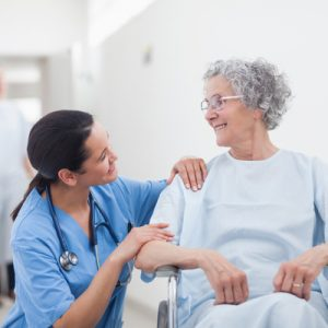 A nurse and patient smile at each other.