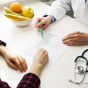 A doctor and patient go over a sheet of paper together.