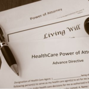 """ACP papers reading """"Living Will"""" and """"HealthCare Power of Attorney"""" with a pen laid on top of them."""