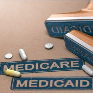 Stamps reading Medicare and Medicaid with pills scattered over them