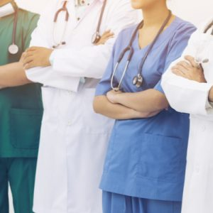 A primary care team in scrubs or white coats, arms folded.