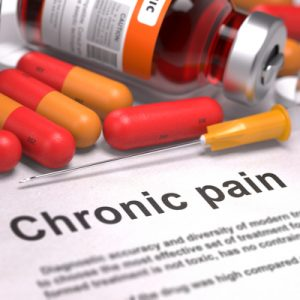 "Pill bottle and red and orange pills over a sheet reading ""Chronic pain""."