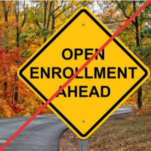 """Yellow road sign reading """"Open Enrollment Ahead"""", with a red strike through the whole image, indicating that it will be difficult for Michigan residents who lost insurance due to COVID-19 to access ACA coverage."""