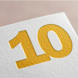 A scorecard with a yellow 10 on it, the age of the ACA