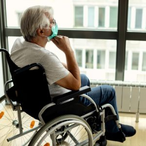 An older adult with a disability looks out a window, seeming lonely and wearing a mask.