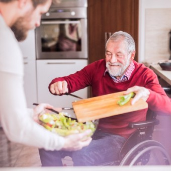 Older gentleman in a wheelchair chopping vegetables for dinner