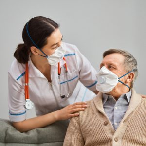 Nurse wearing a mask cares for an elderly man wearing a mask in a nursing home.