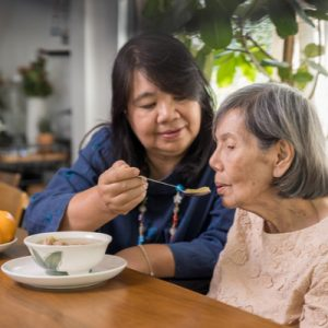 An unpaid caregiver feeds her mother soup.